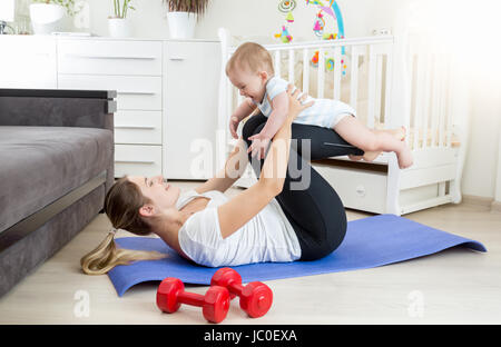 Young beautiful mother doing yoga exercise with her baby on floor at living room - Stock Photo