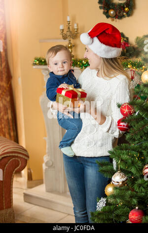 Portrait of happy young mother giving present to her baby son on Christmas at living room next to Christmas tree Stock Photo