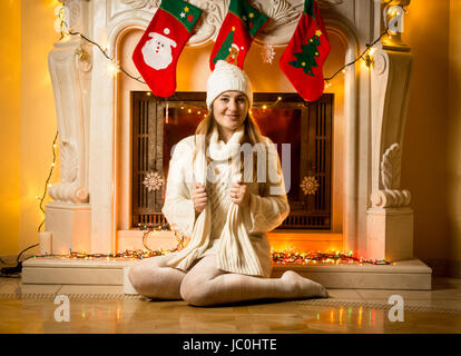 Happy young woman in white sweater sitting at decorated fireplace - Stock Photo