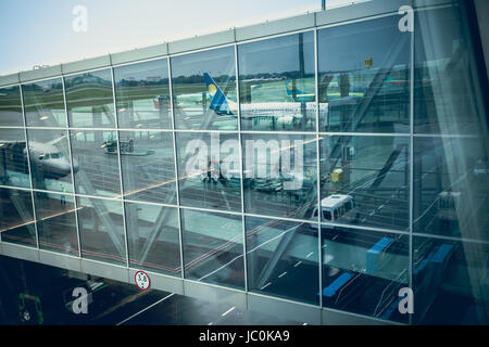 Big airliner reflecting in glass wall of modern airport terminal - Stock Photo