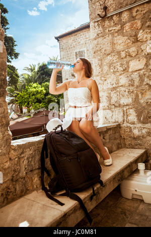 Beautiful young woman with backpack sitting in shadow on street and drinking water - Stock Photo