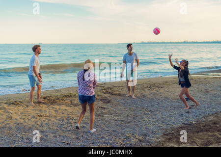 friends playing volleyball on a wild beach during sunset - Stock Photo