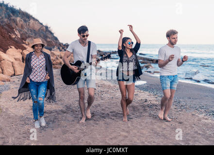 group of young and cheerful friends walking on beach - Stock Photo