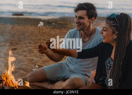 Coupleon a wild beach lit a bonfire and fry marshmallows - Stock Photo