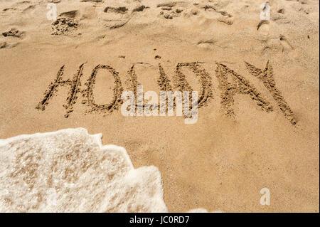 Word 'Holiday' written on wet sand on the seashore - Stock Photo