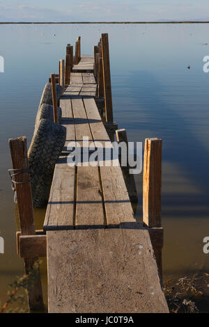 Rickety old wooden dock constructed from odds and ends at the Salton Sea, California. Still used by fishermen. - Stock Photo