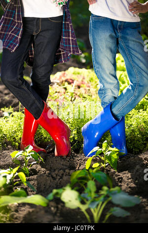 Two girls in colorful gumboots posing on garden bed at hot summer day - Stock Photo