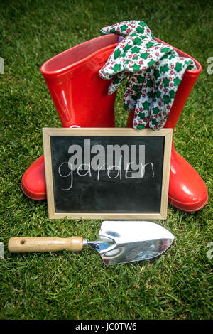Blackboard on the fresh green grass next to garden tools with text 'Garden' - Stock Photo