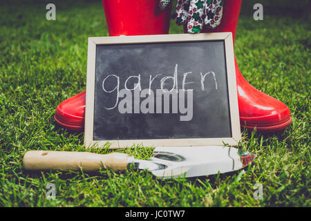 Toned closeup photo of blackboard with word 'Garden' lying on grass next to garden tools - Stock Photo