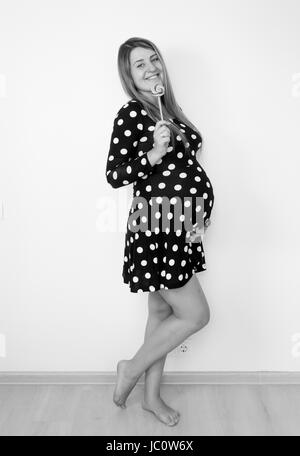 Black and white portrait of cute pregnant woman posing with lollipop - Stock Photo