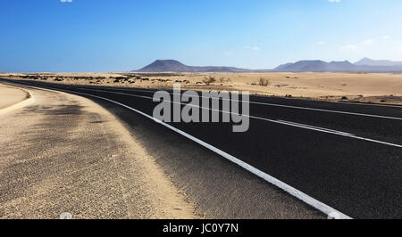 Winding road through the dunes of Corralejo desert with volcano in the background, in Fuerteventura, Canary Islands, - Stock Photo