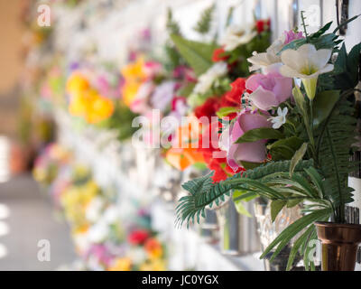 Graves with flowers on a wall of a European cemetery. Vercelli, Italy, Europe. - Stock Photo