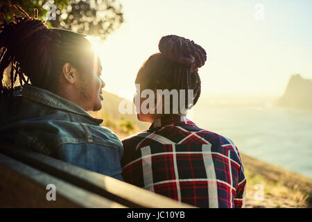 Couple of African descent sitting on a public viewpoint bench - Stock Photo