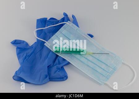 Schutz vor Ansteckung, Mundschutz, Handschuhe und Spritze auf hellem Hintergrund - Stock Photo