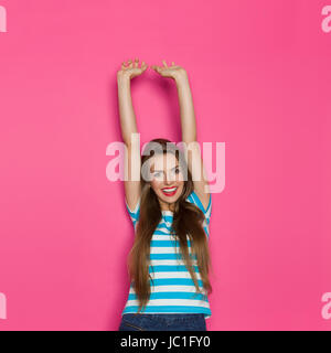 Smiling young woman in blue striped holding arms raised and looking at camera. Waist up studio shot on pink background. - Stock Photo