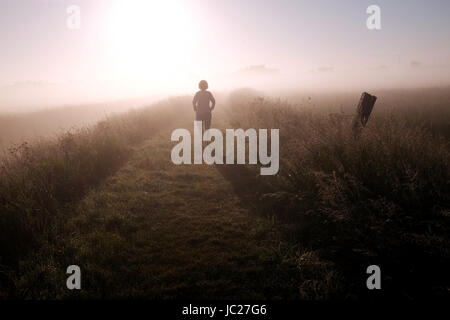Aldeburgh Suffolk, UK. 14th June, 2017. A walker is shrouded in a beautiful early morning mist as it is burnt off - Stock Photo