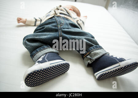 Closeup photo of baby boy feet in jeans and sneakers lying on bed - Stock Photo