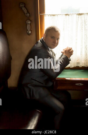 Toned portrait of elegant businessman traveling in old train - Stock Photo