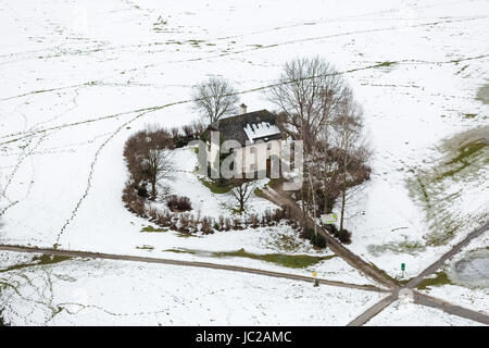 Aerial view on lonely house in field covered by snow at Austria - Stock Photo