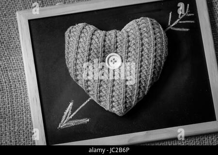 Black and white photo of drawn by chalk arrow going through knitted heart - Stock Photo
