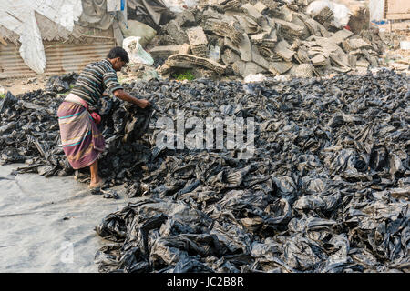 A man is sorting out recyclable plastic materials in Dhapa Garbage Dump - Stock Photo