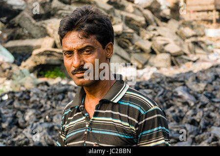 Portrait of a man sorting out recyclable plastic materials in Dhapa Garbage Dump - Stock Photo