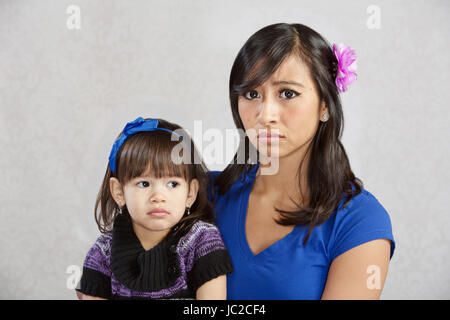 Disappointed Asian mother holding serious female toddler - Stock Photo