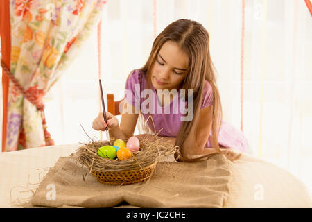Portrait of cute girl decorating easter eggs in basket - Stock Photo