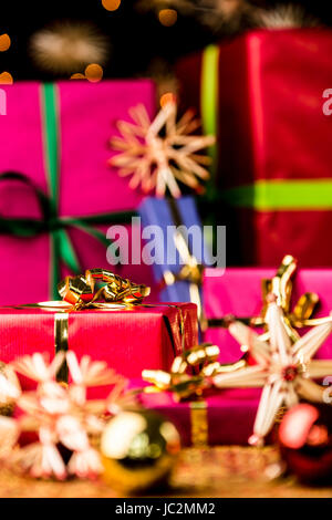 Six Christmas presents in monochrome gift-wrapping. Focus is set on the golden bow around the small crimson red - Stock Photo