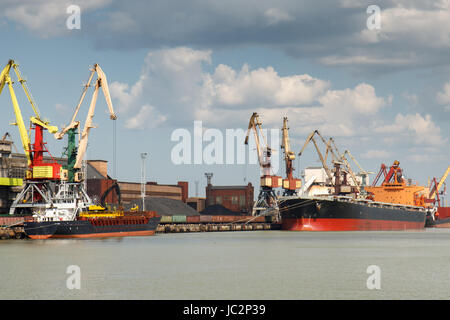 Industrial harbor with two freight ships with coal being loaded in - Stock Photo