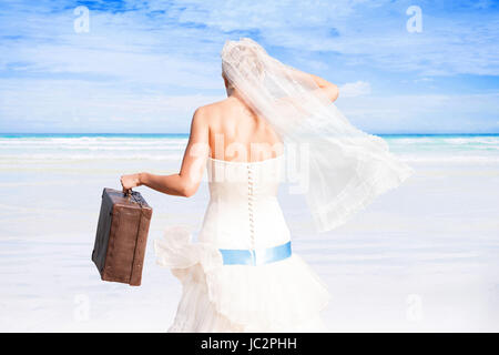 Beautiful bride with antique suitcase in white wedding dress on white sand beach with turquoise ocean on sunny day. - Stock Photo