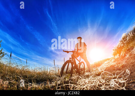 Low angle view of cyclist standing with mountain bike on trail at sunrise. Attractive sportsman in the sportwear - Stock Photo