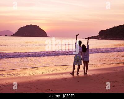 young asian couple taking a walk on beautiful beach before sunrise. - Stock Photo