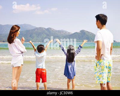 asian family with two children having fun on beach. - Stock Photo