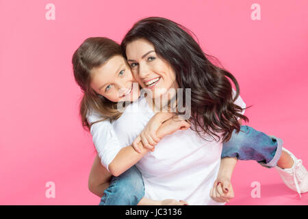 Happy beautiful mother and daughter hugging and smiling at camera - Stock Photo