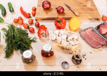 Close-up view of fresh vegetables and raw meat on wooden table - Stock Photo