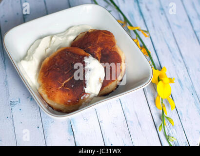 Fritters with cheese in a square plate. Fried pancakes on a blue wooden background - Stock Photo