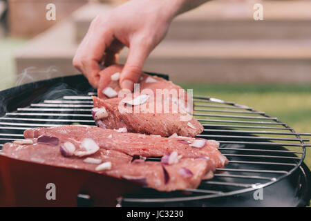 man roasting meat with onion on barbecue grill - Stock Photo