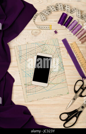 Sewing accessories, fabric, patterns and a mobile phone of white color on a light wooden background. Selective focus.