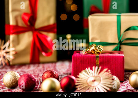 Red present within shallow depth of field. Golden and green gifts with bow knots in the back. Christmas baubles - Stock Photo