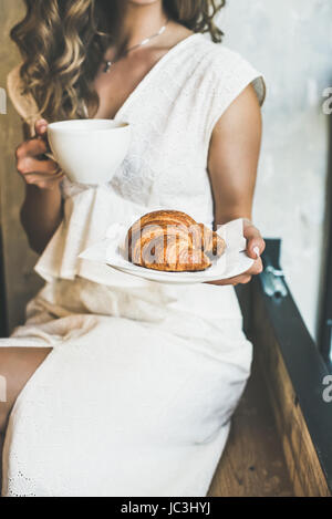 Blond woman holding fresh croissant and cup of cappuccino - Stock Photo