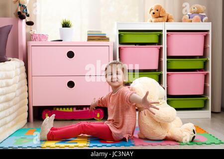Cute little girl with a big teddy bear sitting on the floor in the children's room - Stock Photo