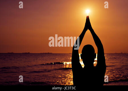 the silhouette of a young caucasian man practicing yoga in front of the sea in backlight - Stock Photo