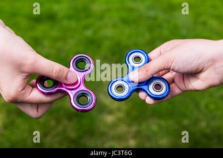 Kid hands with popular toy fidget spinners - Stock Photo
