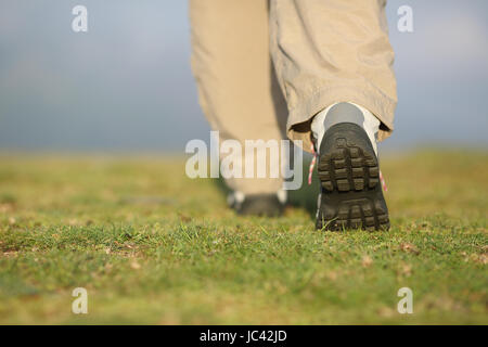 Back view of hiker legs with boots walking on the mountain with an unfocused background - Stock Photo