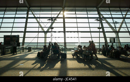 Passengers in silhouette waiting at sunlit departure gate for early morning flight, Shanghai Pudong International - Stock Photo