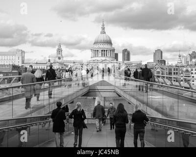 LONDON, ENGLAND, UK - MARCH 04, 2009: Tourists crossing the Millennium Bridge linking the City of London with the - Stock Photo