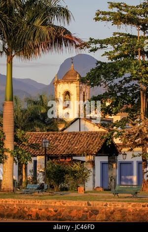 Evening mood in colonial town Paraty with Igreja de Santa Rita, colonial buildings and tropical hills, Brazil - Stock Photo