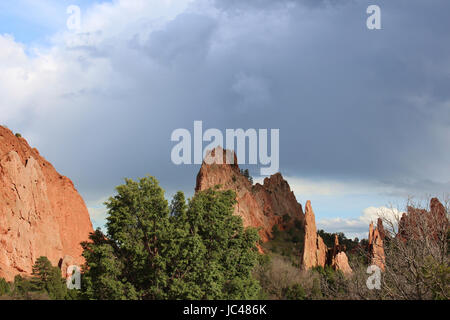 Red rock pinnacle formations rising behind various trees under partially stormy skies at the Garden of the Gods - Stock Photo