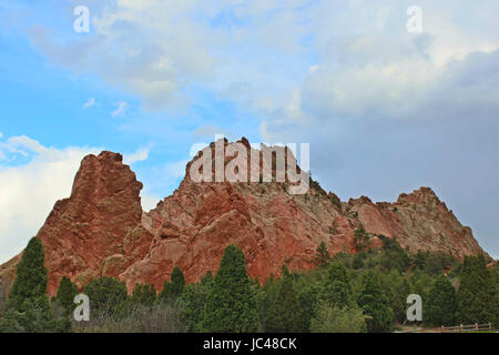 Large rock formation, made of red rock, and evergreentrees along a hiking trail at the Garden of the Gods in Colorado - Stock Photo